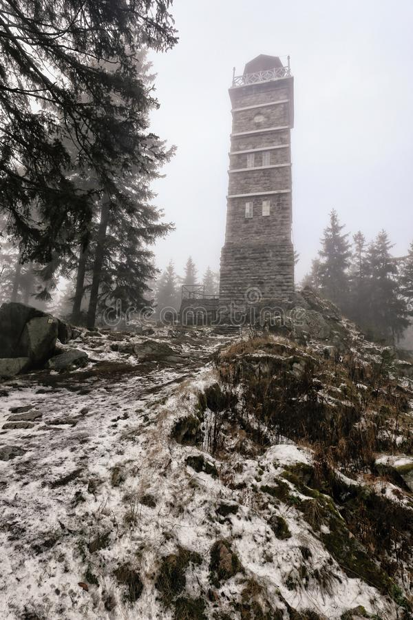 Old rectangular outlook tower on the top of snow covered hill. Old stony rectangular outlook tower on the top of snow covered peak royalty free stock photos