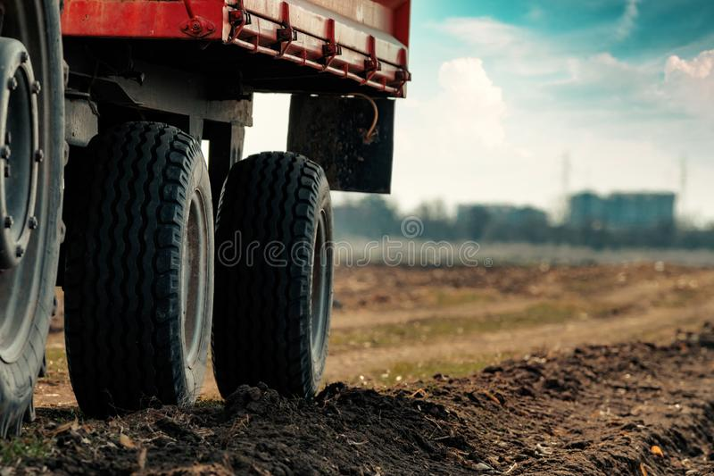 Old red agricultural tractor with trailer on dirt countryside road. In spring afternoon stock image