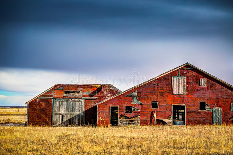 Old Red Barn. An old red barn on the prairie in Colorado. There is brown grass in front of the barn and a dark ominous sky above stock images