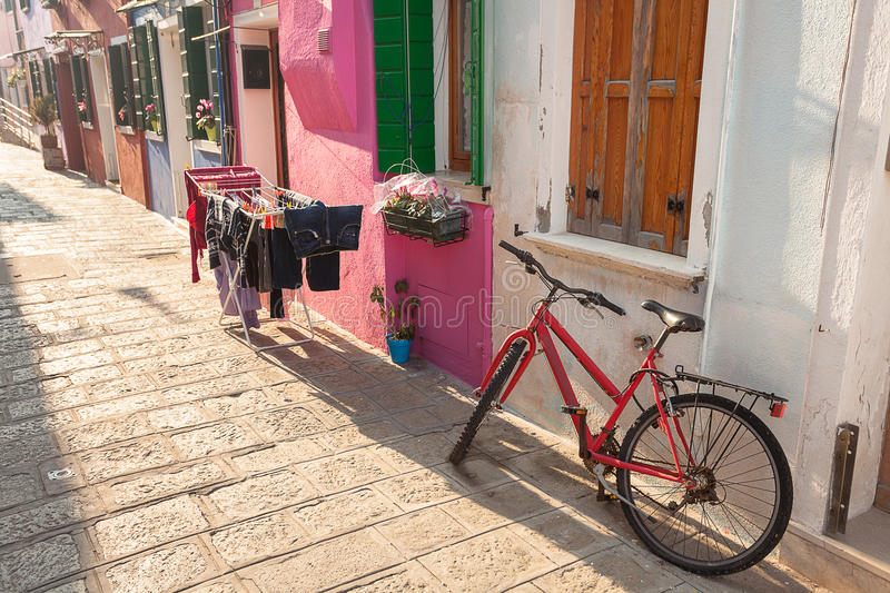 Old red bicycle parked long an external wall in Burano island, V royalty free stock photography