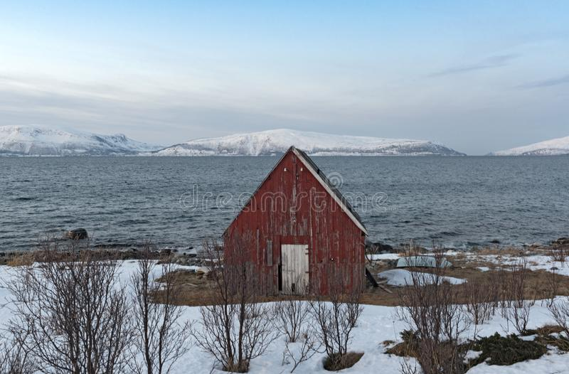 Old red boathouse at the shore of the Ullsfjord in County Troms Norway.  royalty free stock images