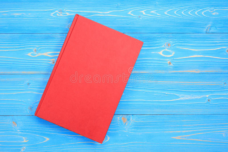 Old red book on wooden plank background. Blank empty cover for d royalty free stock images