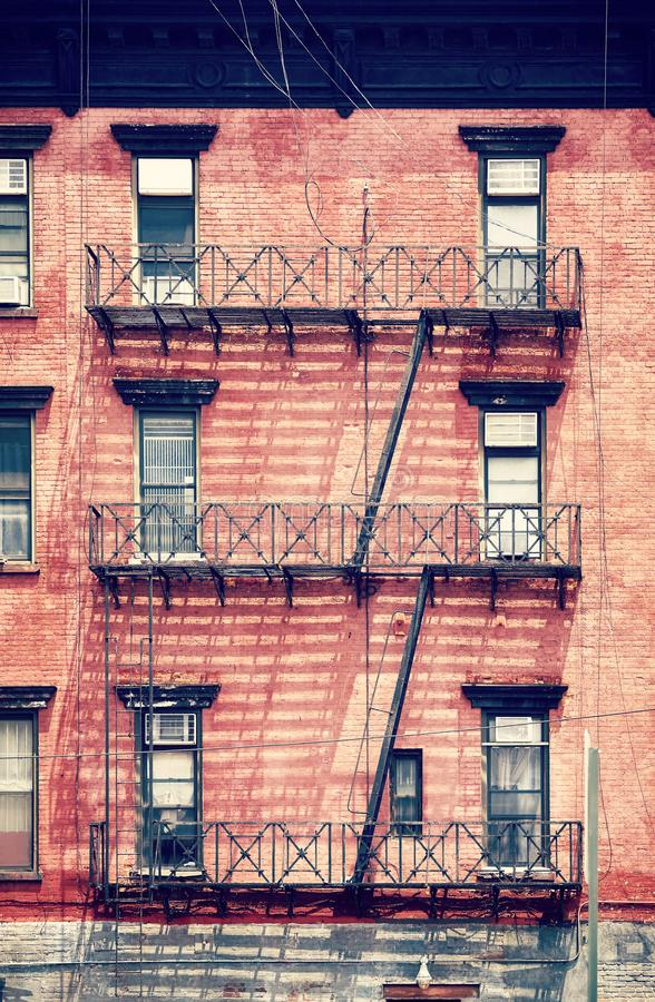 Old red brick building with fire escapes, New York City. Old red brick building with fire escapes, one of the New York City symbols, color toned picture, USA stock image