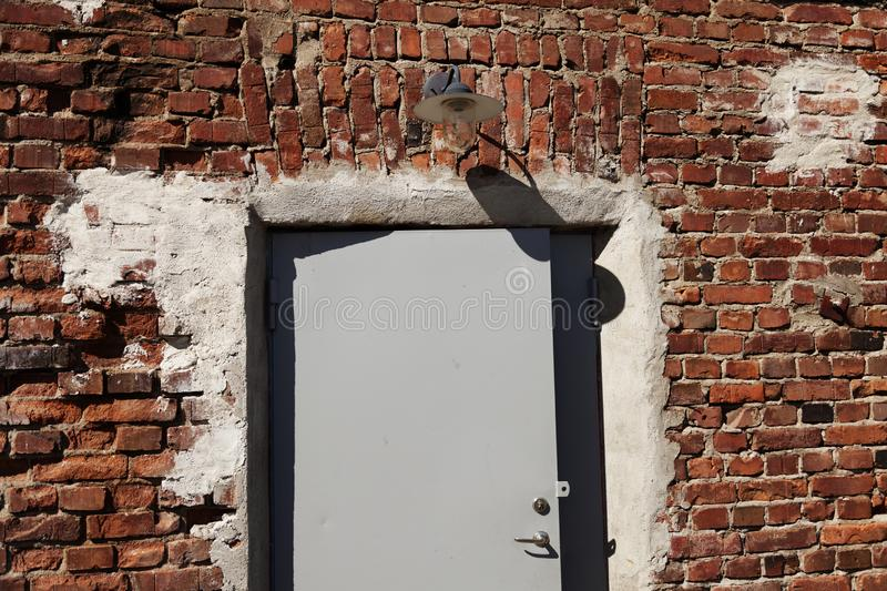 An old red brick building with new plate door and lighting stock images