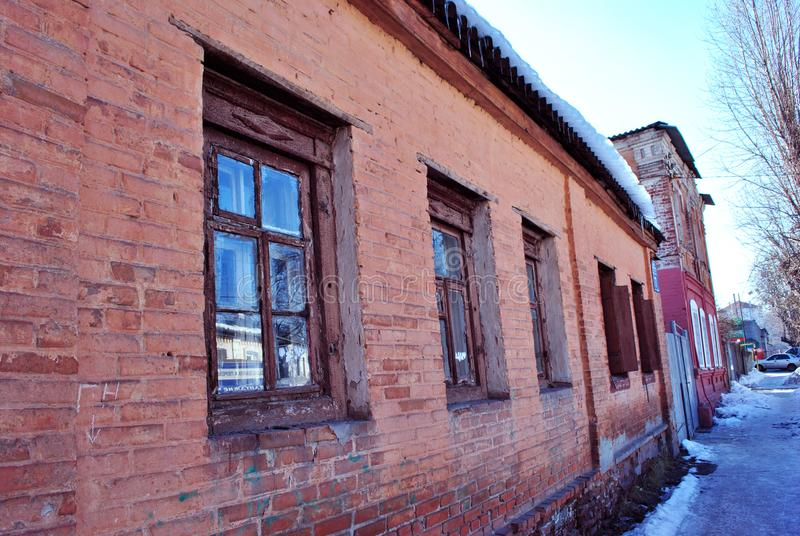 Old red brick building wall with windows close up, small town winter street, snow on roof and poplar tree without leaves, bright. Old red brick building wall stock photography