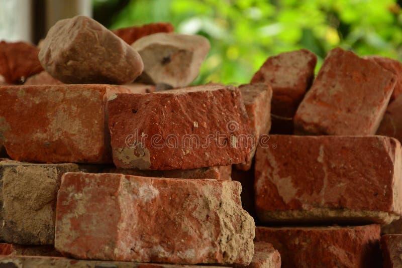 Old red brick clinker pile in te sunlight, cracked bricks stock photo