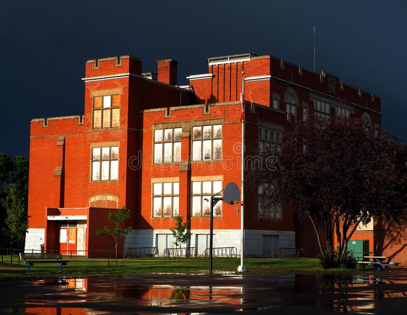Red Brick School With Dark Storm Clouds And Rain. Old red brick school house with dark storm clouds and rain in Edmonton Alberta royalty free stock photo