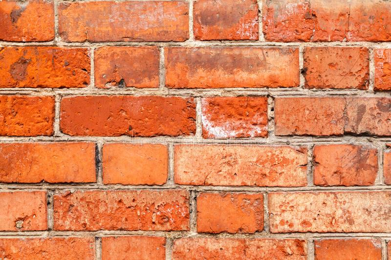 Old red brick uneven wall background. Close-Up of an Old Exterior Brick Wall, grunge background stock image