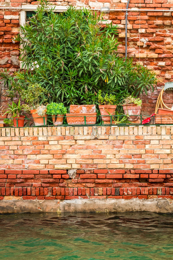 Old red brick wall along a canal in Venice royalty free stock photo