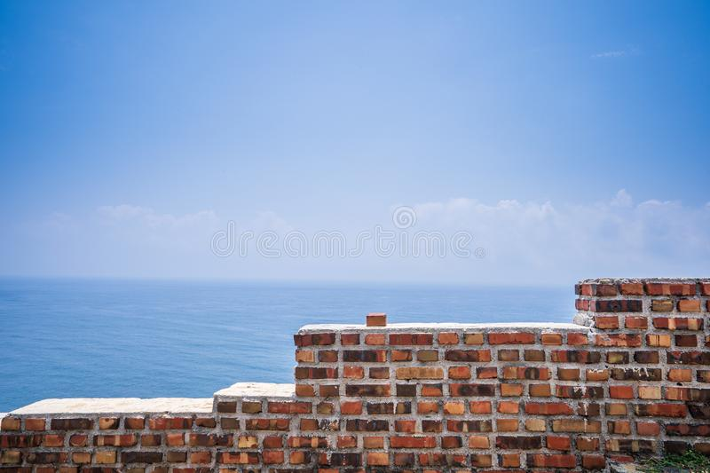 Old red brick wall with beautiful blue sky and white cloud in penghu ,Taiwan royalty free stock photography