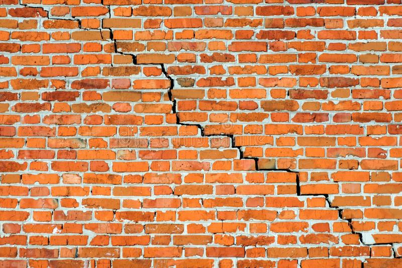 Old red brick wall with big crack. Background stock image