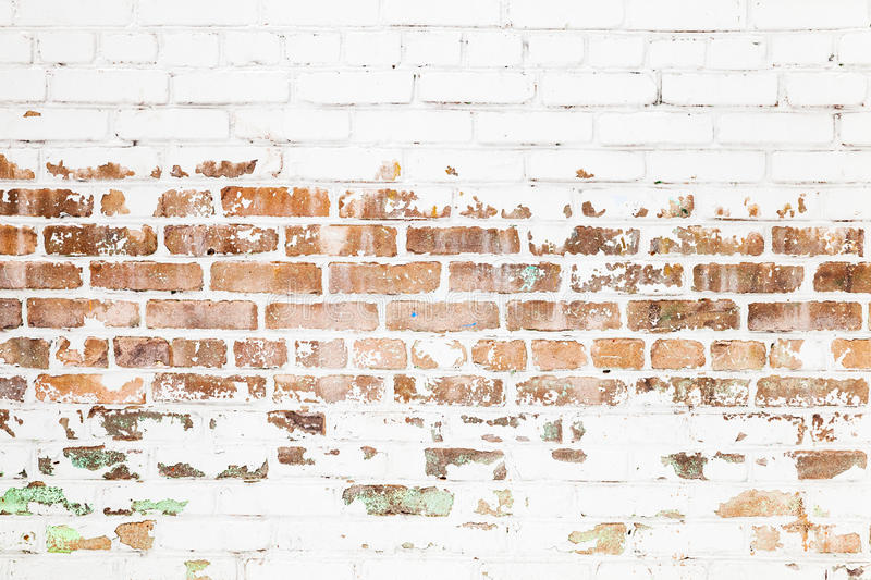 Old red brick wall with damaged white paint layer stock photo