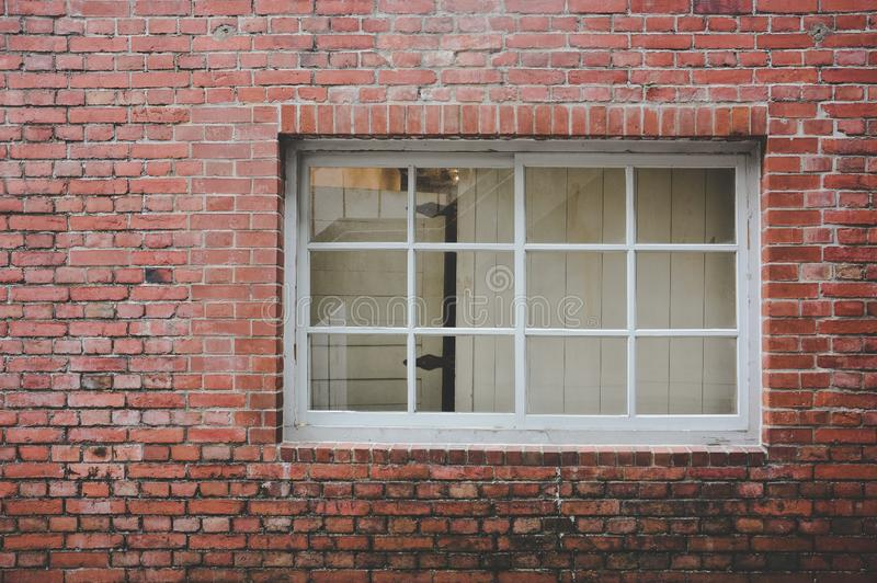 Old red brick wall texture background with classic white wooden frame and sash window with glass panels, copy space stock photos