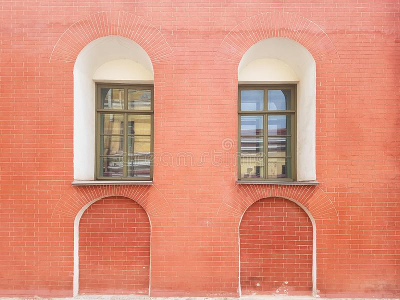 An old red brick wall and two green windows on it. Background stock photos
