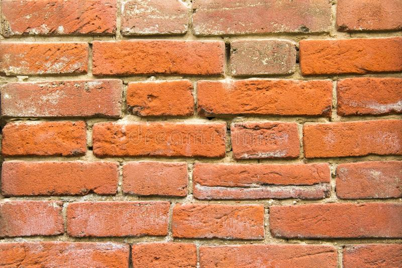 Old red vintage bricks in the wall close up. Old red bricks wall texture close up. Renewed retro house stock photo