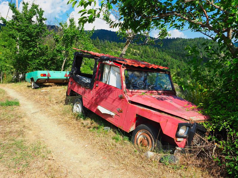 Old Red Car and Green Trailer Abandoned in Rural Area royalty free stock photography