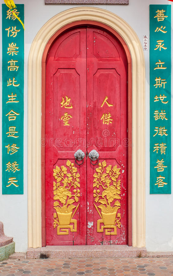 Old red chinese temple door with crave leaf.  royalty free stock images
