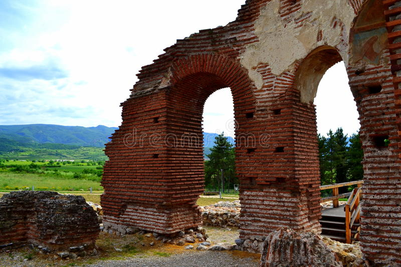 Old red church ruins view. Arched entrances of an ancient Red Church and scenic view.Experts believe that the open two layers of murals are made between VI and royalty free stock photography