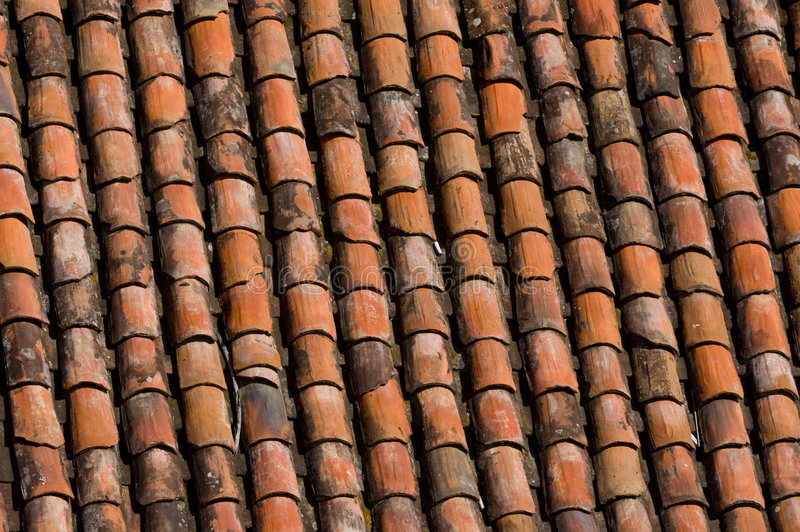 Old red clay roof tiles. Close up of rows of old red clay roof tiles on rooftop royalty free stock photo