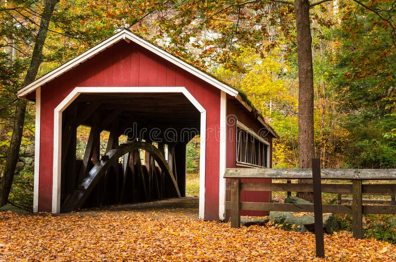 Old Covered Bridge in a Forest in Fall stock photo