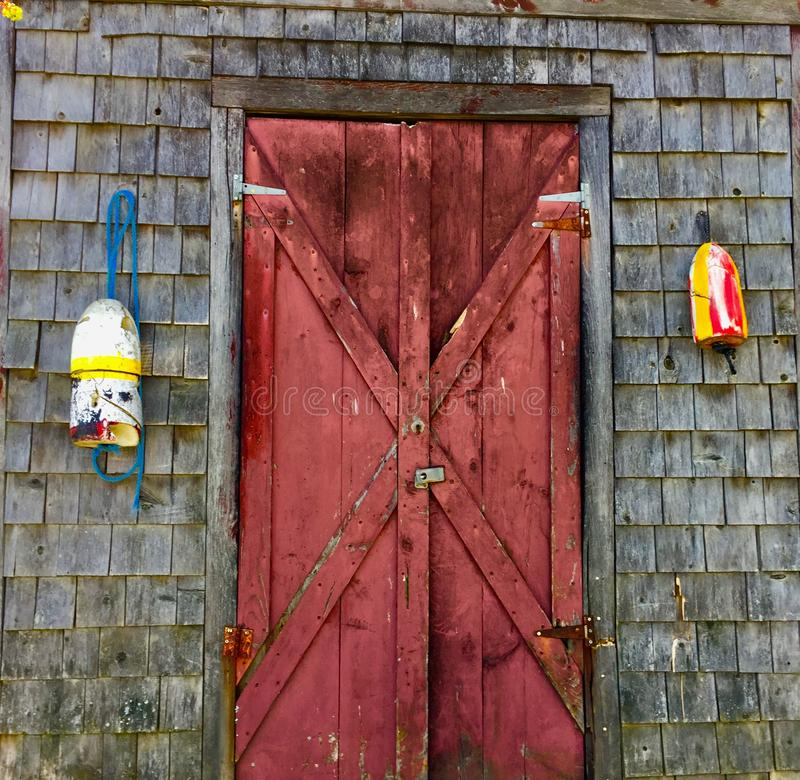 Old red door on clapboard building with buoys stock image