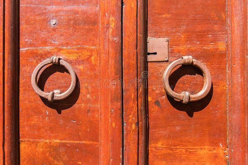 Old red door with round metal handles. Orte, Italy. Old vintage red door with round metal handles. Orte, Italy royalty free stock image