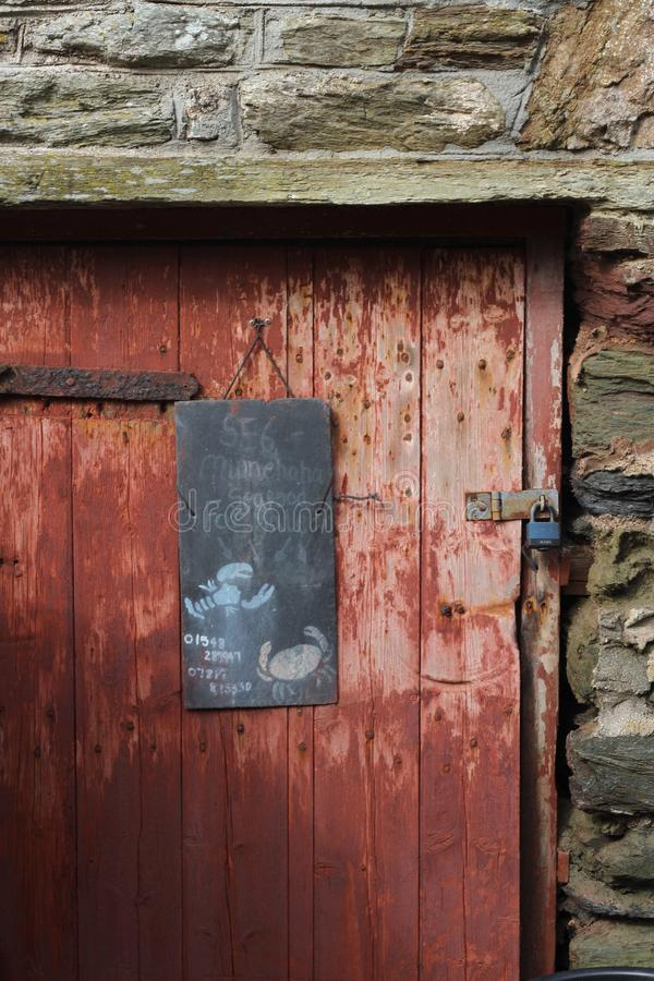 Old red door on surrounded by Devon stone, United Kingdom. Old faded red door surrounded by Devon stone. A chalk sign hung with a lobster and crab illustration stock image