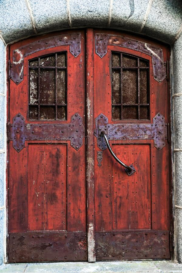 Old red door with wrought bolts and metal trim. Old texture royalty free stock photo