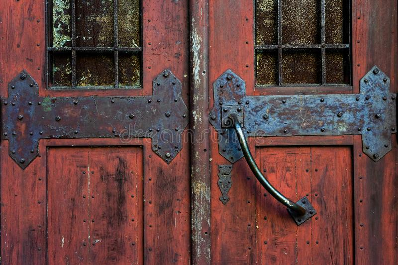 Old red door with wrought iron bolts. Old locks stock photo