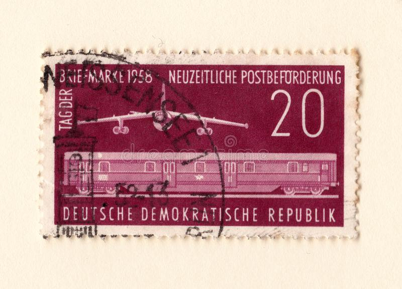 An old red east german stamp with an image of a jet bomber and railway train carriage royalty free stock photos