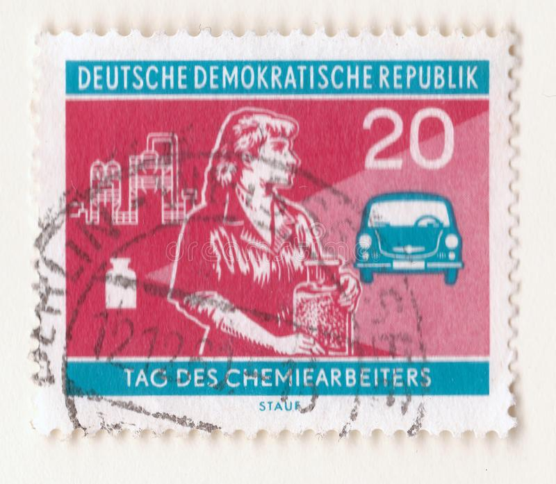 An old red east german stamp with an image of a woman chemist holding a jar with an automobile and industrial factory in the backg royalty free stock photography