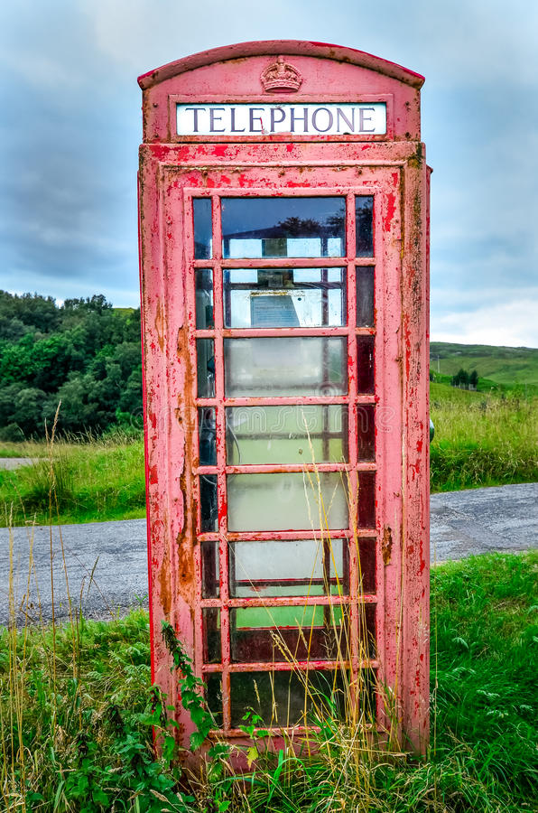 Old red English phone booth in countryside. Detail of old red English phone booth in countryside, United Kingdom royalty free stock photos