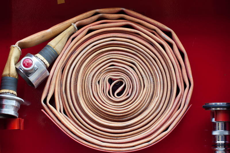 Old red fire hose stock images