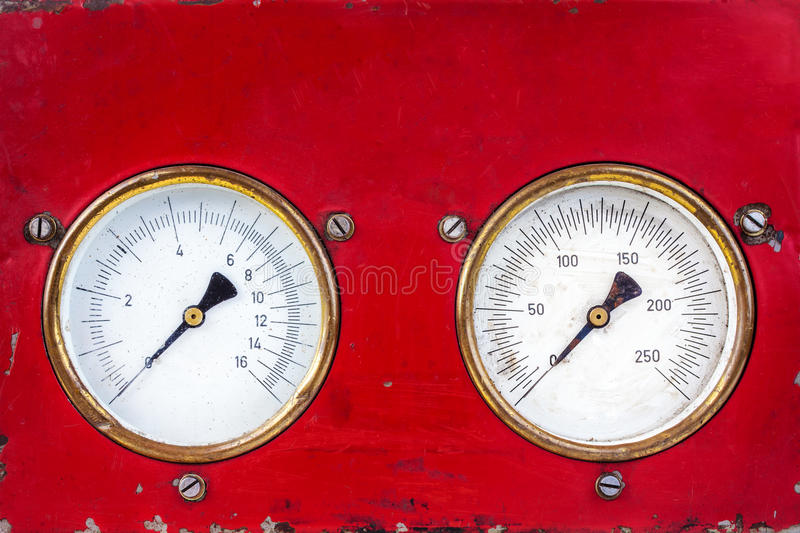 Old red industry panel with two analog meters. Old red industry panel with two round measurement meters royalty free stock image