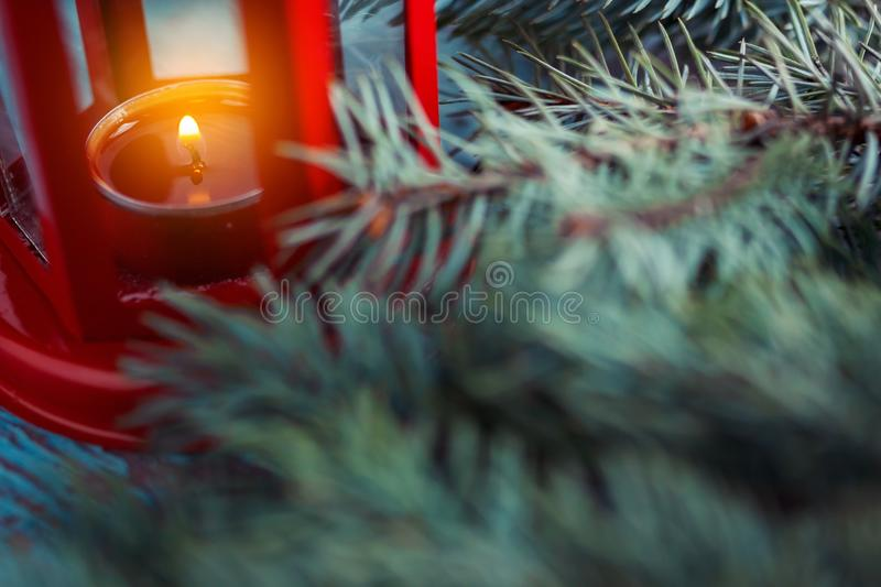 old red lantern with a lighted candle inside and Christmas tree stock images