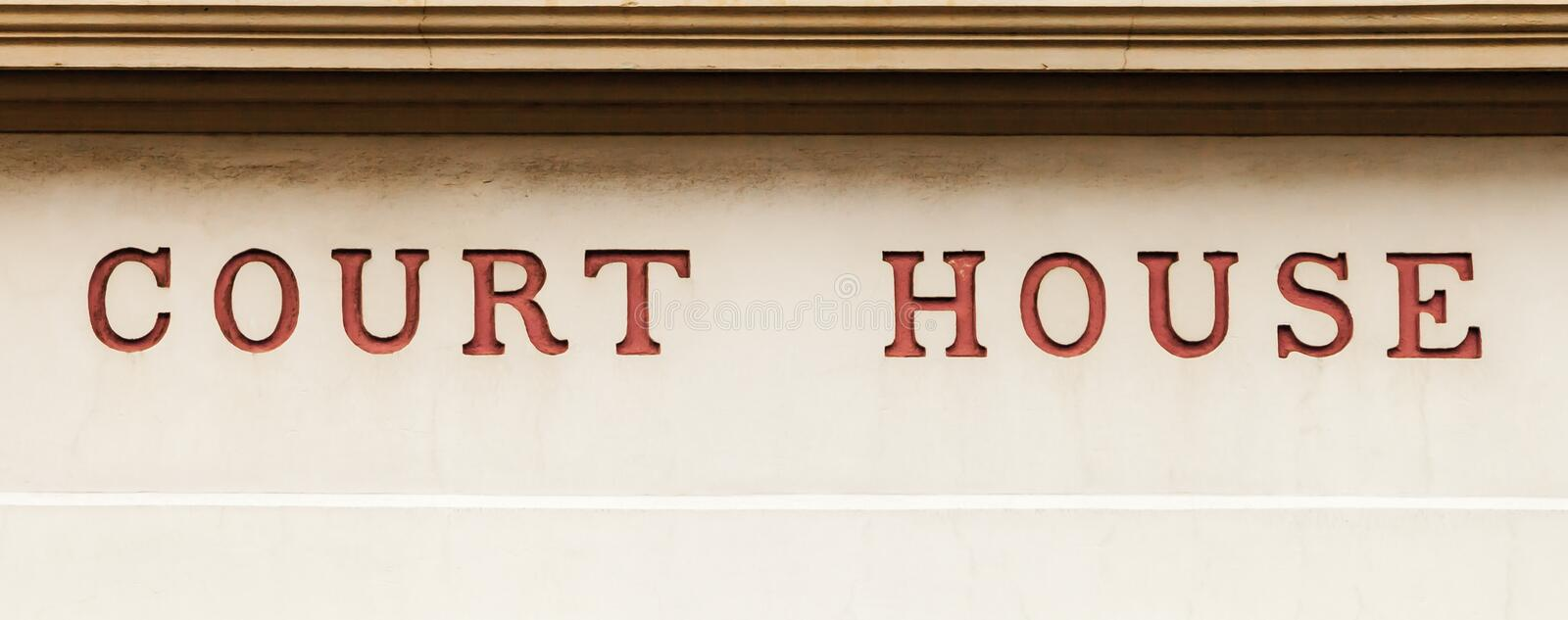 Old Red Letters on Public Historic Building Stating COURT HOUSE. Old red painted inset letters stating COURT HOUSE on a dirty grimy public historic heritage royalty free stock images