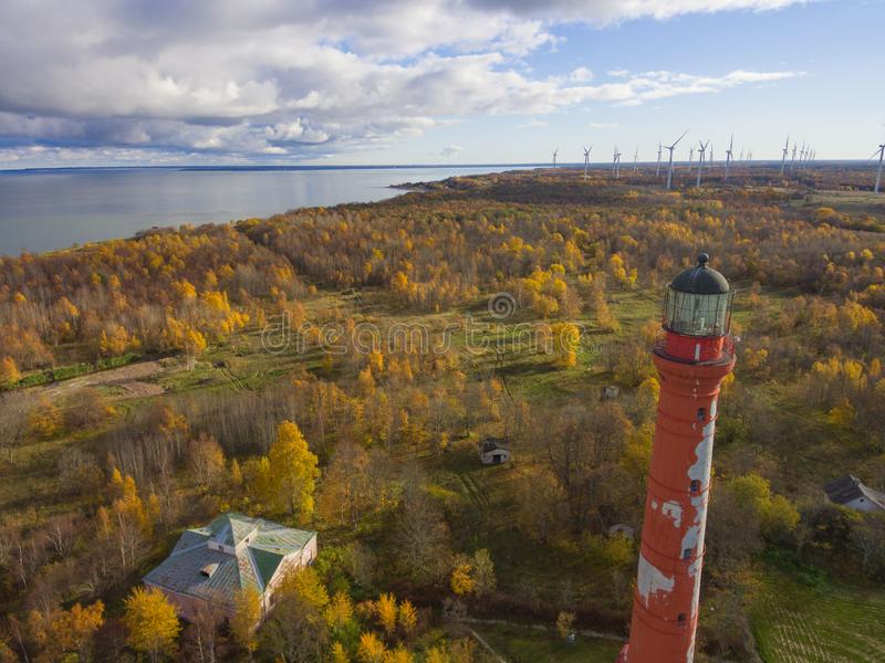 Old red Lighthouse in Paldiski, Estonia staying on a seacoast of. Baltic Sea with the green energy windmills on the background stock photography