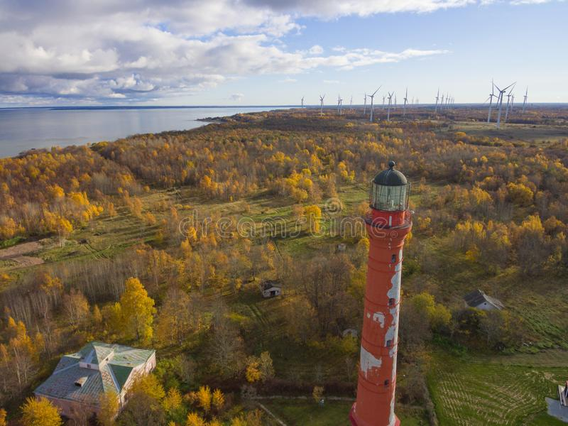 Old red Lighthouse in Paldiski, Estonia staying on a seacoast of. Baltic Sea with the green energy windmills on the background royalty free stock images