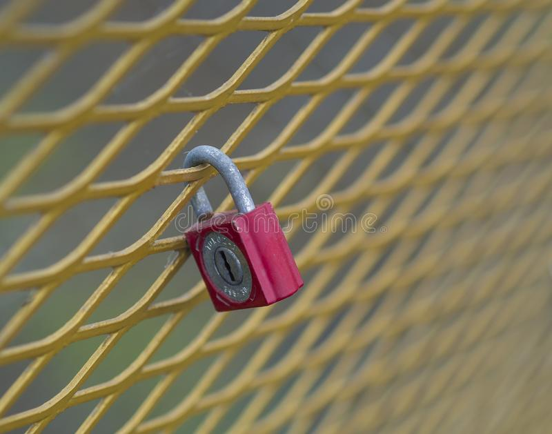 Old red lock hanging locked on the yellow metal grating. Close up old red lock hanging locked on the yellow metal grating royalty free stock photos