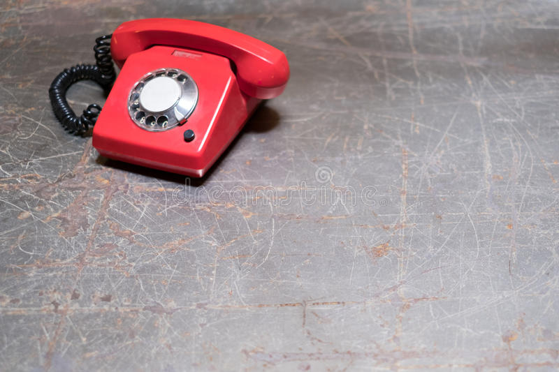Old red phone on table - vintage telephone on desk stock photography