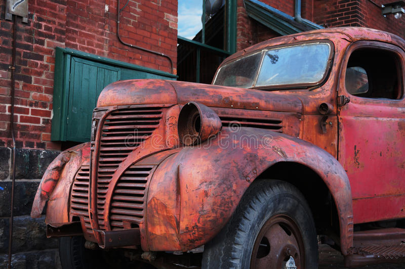 Old Red Pickup Truck in Distillery District of Toronto. Against a red brick wall stock photo