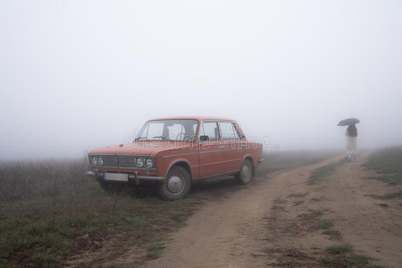 Old red retro car stands in fog near the dirt road, girl in white coat walks under umbrella on the background. Autumn time royalty free stock image