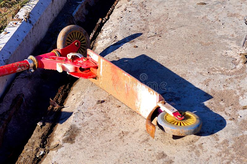 Old red rusty abandoned scooter lying on the concrete floor. Childrens transport royalty free stock image