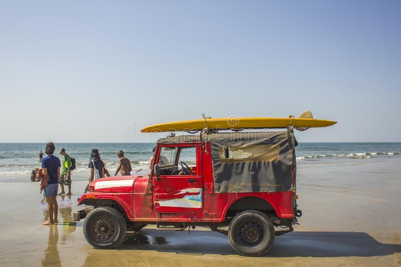 Old red sea rescue car with a yellow surfboard on the roof against the sandy beach and the ocean. Arambol, Goa/India - 04.01.2019: old red sea rescue car with a royalty free stock photo