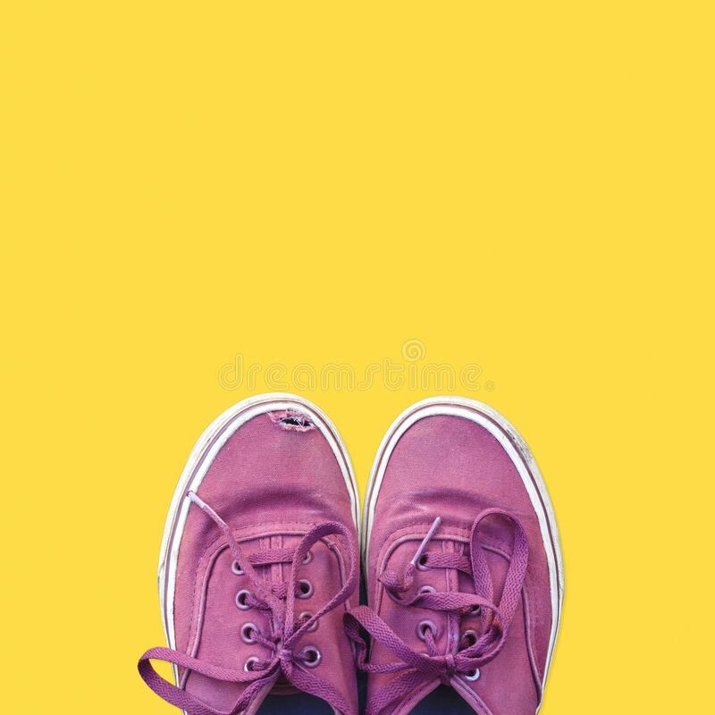Old red sneakers on yellow background stock images