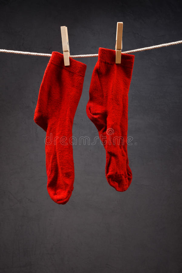 Old red socks hanging on rope stock photo