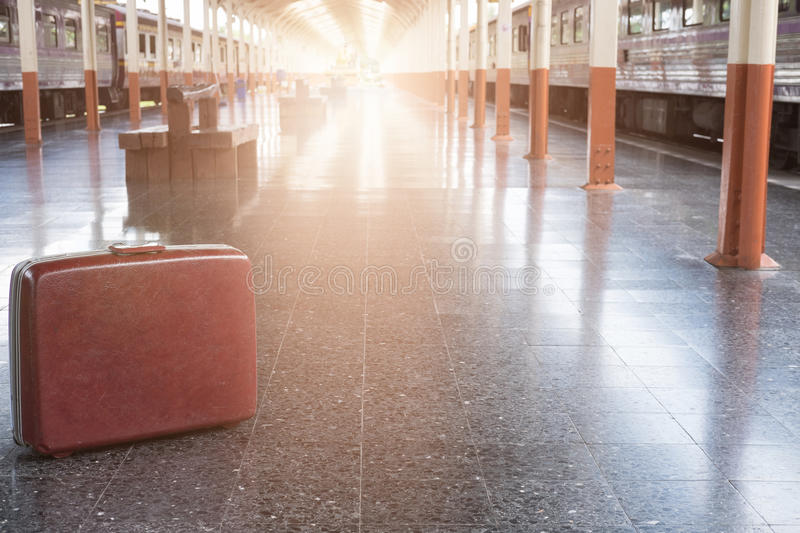 old red suitcase, baggage or luggage on platform at train station. journey, trip, travel concept royalty free stock photo