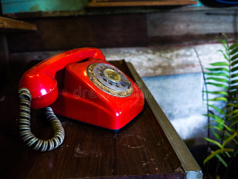 Old red telephone placed on an old wooden desk. The back has light blue wood and brown. And green trees.  royalty free stock photos
