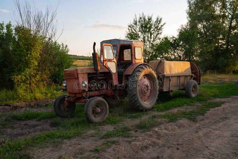 Old red tractor with a tank, barrel sprayer standing near a dirt road. And the garden royalty free stock photo