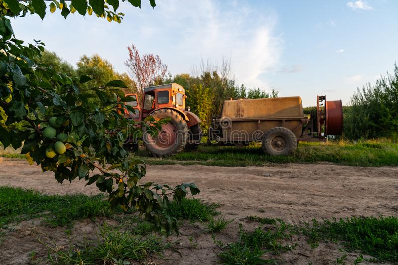 Old red tractor with a tank, barrel sprayer standing near a dirt road. And the garden stock images